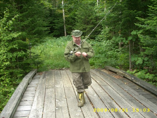 Photo of George Clark Stone walking across wilderness bridge with fishing pole